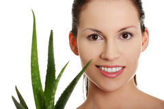 Young beautiful woman's face and aloe vera. Stock Photo