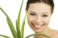 Young beautiful woman's face and aloe vera. Royalty Free Stock Image