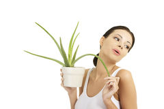 Young beautiful woman's face and aloe vera. Royalty Free Stock Images