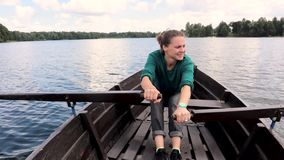 A young beautiful woman is sailing on a boat on the lake. A strong woman paddles with oars stock video