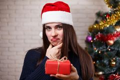 Young beautiful woman in Santa cap discontented with a present. New Year, Christmas, gift, surprise, celebration, emotions concept stock photography