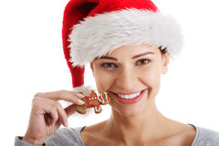 Young beautiful woman in santa hat and a cookie. Royalty Free Stock Photo