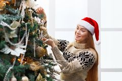 Young beautiful woman decorating christmas tree, new year decoration background Royalty Free Stock Photography