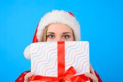 Young beautiful woman in santa hat is hiding her face behind big royalty free stock photography