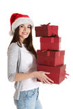 Young beautiful woman in santa hat, holding stock of presents. Stock Photography