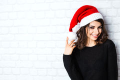 Young beautiful woman in santa hat posing. Royalty Free Stock Photography