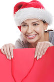 Young beautiful woman in santa hat in red shopping bag. Stock Photos