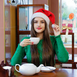 Young beautiful woman in Santas hat drinking tea in cafe Royalty Free Stock Photo