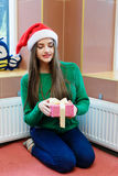 Young beautiful woman in santas hat holding gift box Stock Photo