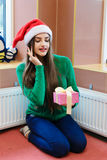 Young beautiful woman in santas hat holding gift box Stock Photography