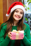 Young beautiful woman in santas hat holding gift box Royalty Free Stock Photos
