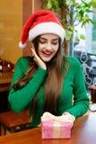Young beautiful woman in santas hat looking at gift box Stock Images