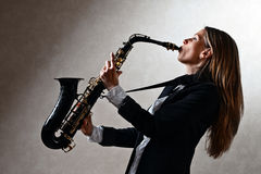 Young beautiful woman with saxophone Royalty Free Stock Photos