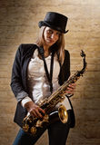 Young beautiful woman with saxophone Royalty Free Stock Images