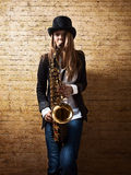 Young beautiful woman with saxophone Royalty Free Stock Photography