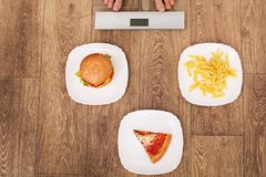 A young beautiful woman is on the scales. To choose between potato chips, pizza and burgers. The concept of healthy eating. Health Royalty Free Stock Photo