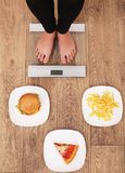 A young beautiful woman is on the scales. To choose between potato chips, pizza and burgers. The concept of healthy eating. Health royalty free stock images