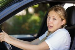 Young beautiful woman scared and stressed while driving car. Woman royalty free stock images