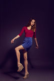 Young beautiful woman in scarlet kombidress, suede skirt.  Fashi Royalty Free Stock Photo