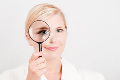 Young beautiful woman scientist with zooming glass Royalty Free Stock Image