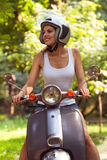 Young and beautiful woman on a scooter on the street and smiling Royalty Free Stock Photography