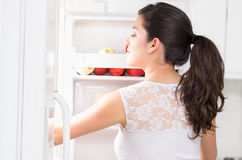 Young beautiful woman searching for food in the. Young beautiful brunette woman searching for food in the fridge stock images