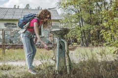 Young beautiful woman searching for water source. At the abandoned summer camp Stock Photos