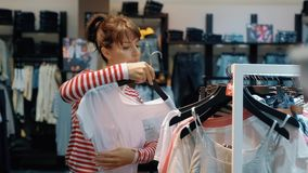 Young beautiful woman seller in a denim store hangs clothes on hangers stock video footage