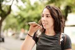 Young beautiful woman sending voice message with her smartphone. Portrait of a young beautiful woman sending voice message with her smartphone. Outdoors stock photography