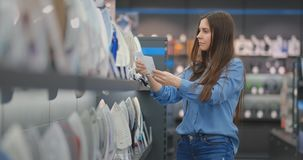 A young beautiful woman in a shirt holding the characteristics of the iron studies the prices and chooses to buy an iron. In the store standing at the counter stock video