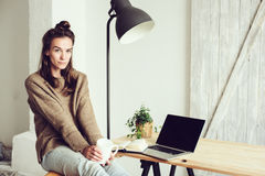 Young beautiful woman shopping at home online with laptop and cup of coffee in the morning. Home office in modern scandinavian interior Royalty Free Stock Photos