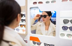 Woman choosing glasses in optician store Stock Photos