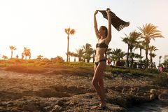 Young woman in bikini  on tropical beach. Young beautiful woman on the shore on tropical beach with holding peace of cloths Stock Photos