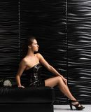 Young beautiful woman in short black dress posing on the couch. Black wavy wall in the background Stock Photography