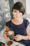 Young beautiful woman with short hair drinking steaming coffee. In a street cafe stock photo