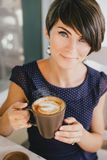 Young beautiful woman with short hair drinking steaming coffee Royalty Free Stock Photography
