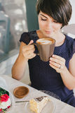 Young beautiful woman with short hair drinking steaming coffee Stock Image