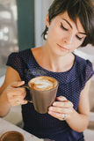 Young beautiful woman with short hair drinking steaming coffee Royalty Free Stock Image
