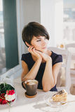 Young beautiful woman with short hair drinking steaming coffee Stock Photography