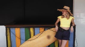 Young Beautiful Woman in shorts and straw hat stands near surf board. In 4K stock video footage