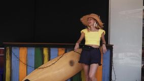 Young Beautiful Woman in shorts and straw hat stands near surf board stock video