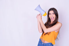Young beautiful woman shouting through a megaphone Royalty Free Stock Photography