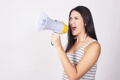 Young beautiful woman shouting through a megaphone. Or loudspeaker. Caucasian woman expressing. Leadership concept Royalty Free Stock Images