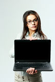 Young beautiful woman showing laptop. On gray background Royalty Free Stock Images