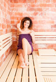 Young beautiful woman showing ok sign when sitting in sauna Royalty Free Stock Photography