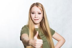 Young beautiful woman shows thumbs up sign. Body language concept. stock image