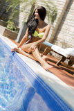 Young beautiful woman on the side of the pool playing with water Stock Images