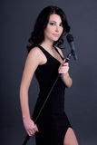 Young beautiful woman singer with microphone over grey Royalty Free Stock Image