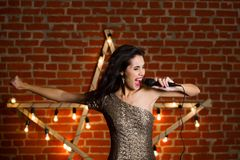Young beautiful woman singing song over wooden star with bright Stock Photos