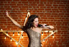 Young beautiful woman singing song over wooden star with bright. Lamps Stock Photography